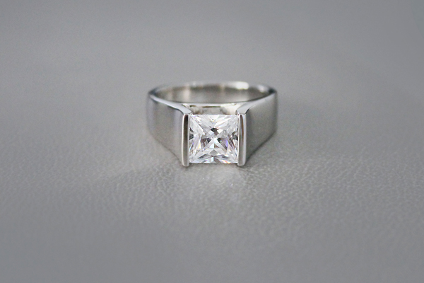 Tension set princess cut diamond engagement ring with wide band.